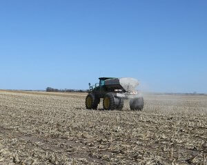 A John Deere tractor driving through an empty field preparing for planting season