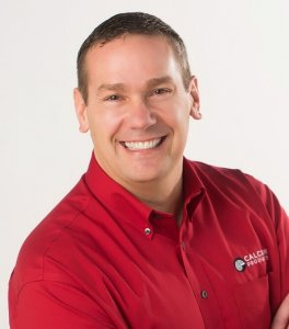 Brent VanEe smiling with his arms crossed in front a white background while wearing a red button up Calcium Products shirt