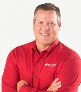 Brian Easland smiling with his hands crossed while wearing a longsleeve button up red shirt with the Calcium Products logo on the left side