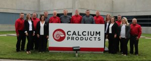 Fifteen men and women in black, gray, red, and white outfits smile while standing behind a large red and white Calcium Products sign in front of the concrete Calcium Products building