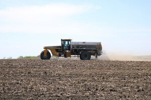 A yellow tractor driving through a field dispensing fertilizer to help crops grow