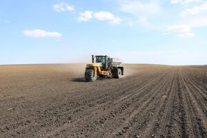 A yellow tractor with one large front while drives along rows of soil to prepare for planting season