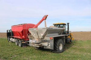 A red and black truck is dispensing fertilizer into the back of a yellow tractor so it can carry it out and distribute it around fields to help crops grow