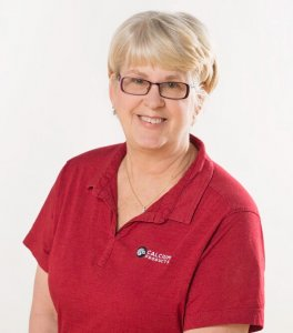Lory Zeman wearing a red Calcium Products polo, a silver necklace, and brown framed glasses in front of a white backdrop