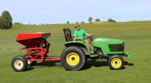 A man in a green shirt, black hat, and khaki pants is riding a small John Deere tractor pulling a red fertilizer cart along a golf grass turf