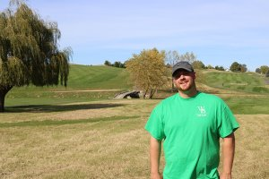 Andy Young wearing a gray Nike hat and a green Woodbine Bend shirt smiles with the Woodbine Bend golf course as his backdrop