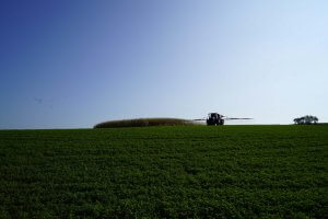 A tractor is seen off in the distance of a field using sprayers to distribute chemicals on the field to help crops grow and eliminate pests