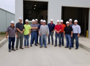 Thirteen men wearing safety glasses and white hard hats stand in front of a gray warehouse and smile for a photo