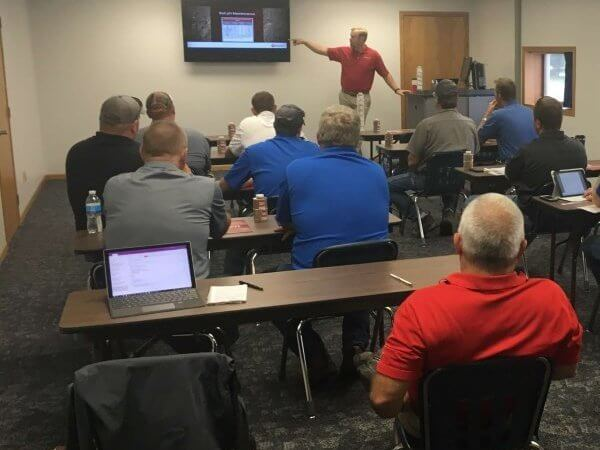 Andrew Hoiberg wears khakis and a red polo as he stands in front of a room of sixteen men to educate them about processes using slides on a television