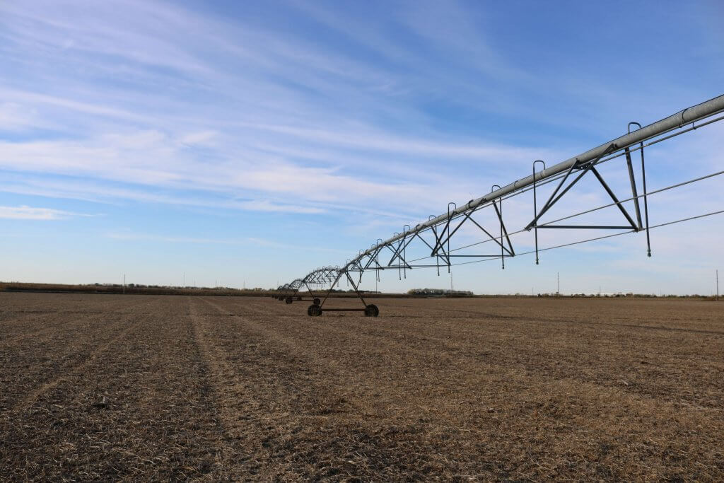 A view of a large farming irrigation system in the middle of a dry brown field with blue skies overhead