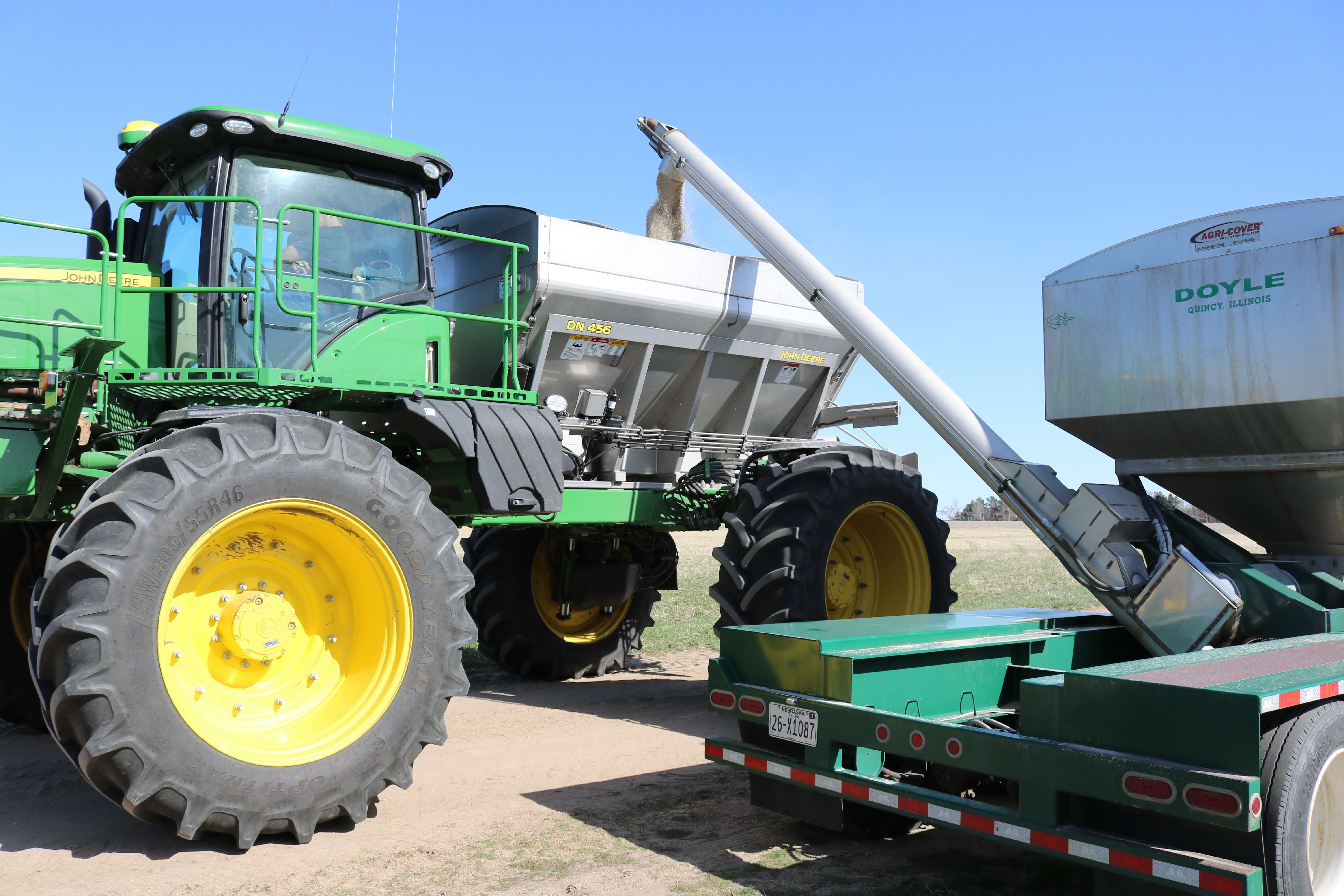 A green and silver Doyle truck is dispensing fertilizer into the back of a green John Deere tractor so it can go out into the field