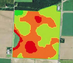 An aerial view of farmland after 98 application. A majority of the land is colored green and orange with minimal spots colored red.