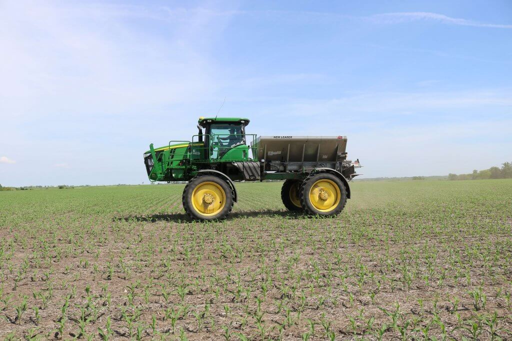 A green and yellow John Deere Tractor with a gray bed behind it sits on top of large yellow and black tires in the middle of a crop field